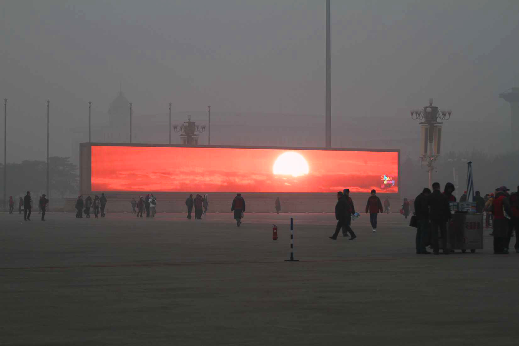 "A video monitor shows the rising sun in Tiananmen Square on January 16, 2014, offering Bejing residents contact with ""nature"" through the thick air pollution. Credit: ChinaFotoPress"